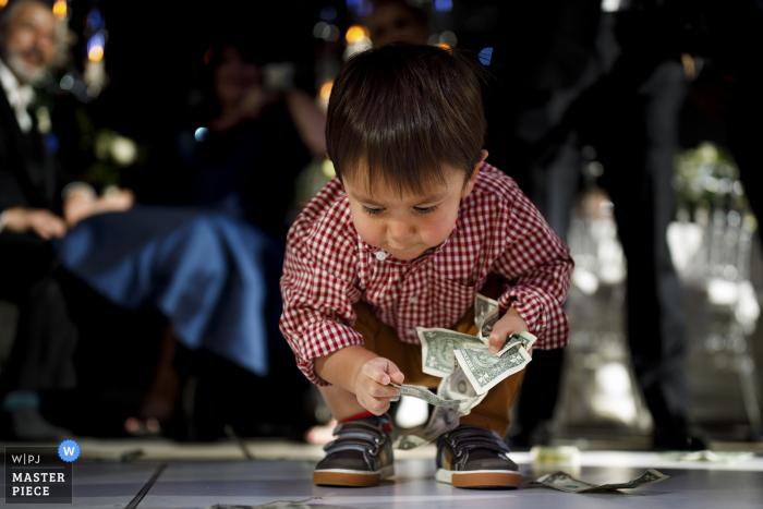 Seawell Ballroom wedding photo showing A young boy picking up dollar bills off the dance floor during a greek wedding