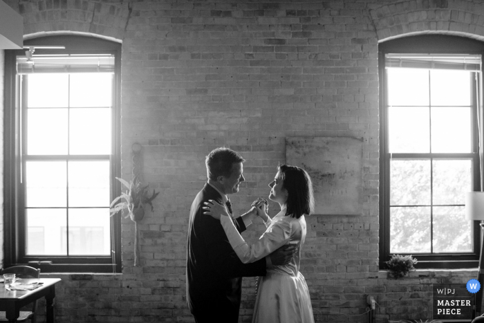 Wedding photograph from the Couple's apartment in Madison, WI showing the Father Daughter Dance in the living room of the couple at their rescheduled wedding