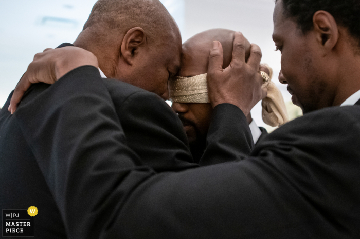 Wedding photo from a New Jersey ceremony showing the father prayerful embrace with son and brother