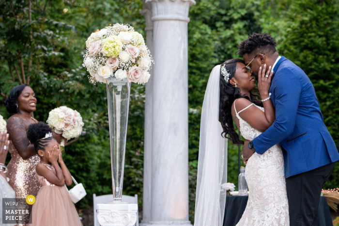 Outdoor Delaware garden ceremony photo of the couple kiss with flower girl who can't take the PDA