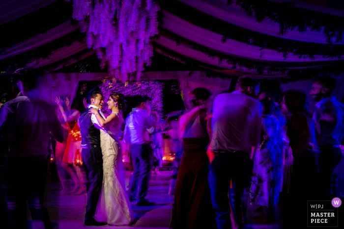 A UK wedding reportage photographer in London created this image of the Bride and Groom dancing under purple lights at the reception party