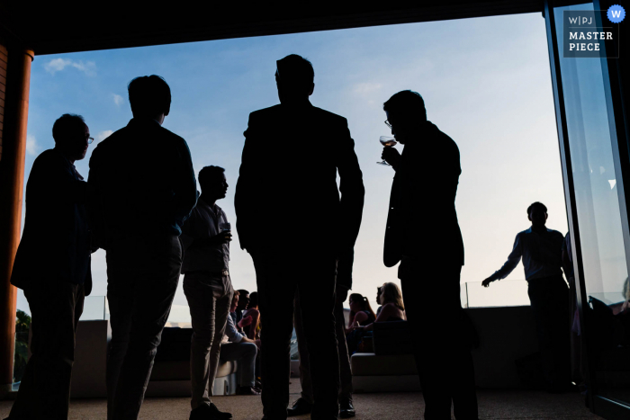 A top wedding photographer in London captured this picture ofGuest having drinks silhouetted against the blue sky