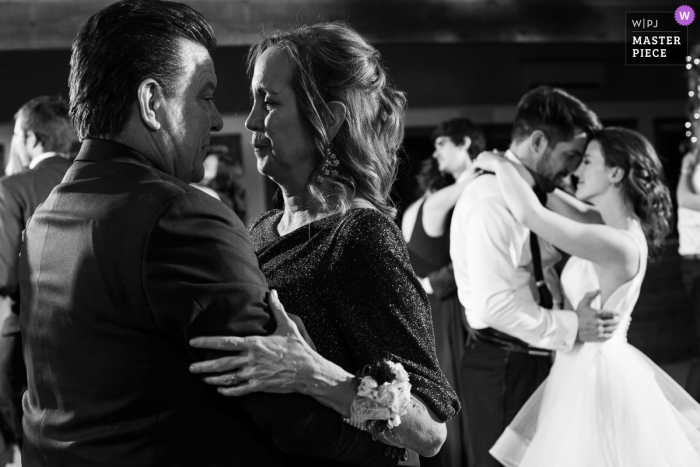 A top wedding photographer in Allenspark, CO at the Wild Basin Lodge captured this picture of the grooms parents sharing a romantic dance at their wedding reception
