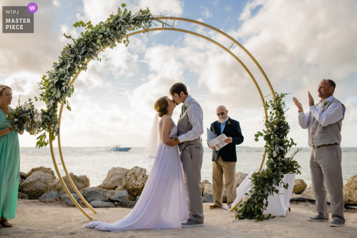 A wedding photographer in Key West, Florida at Fort Zachary Taylor Park created this image ofthe couple with their love of boats as one passed by as they kissed for the first time as husband and wife at the outdoor ceremony