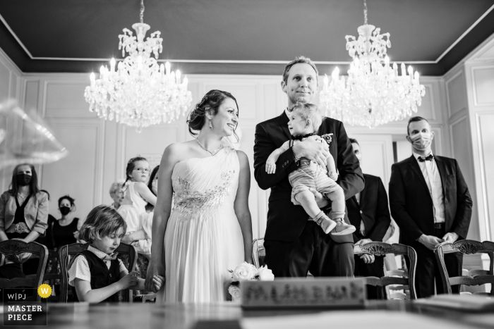 A top wedding photographer in Rennes, Brittany captured this picture ofthe groom holding a young child at the civil marriage counter during the ceremony