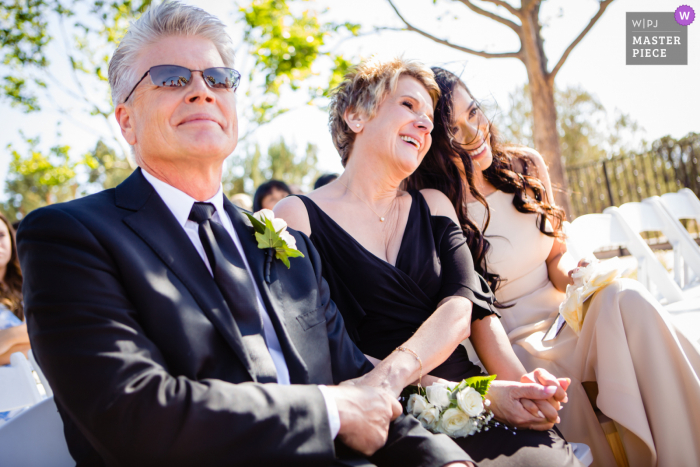 Sky Ranch Lodge, Sedona Arizona wedding photography showing Brides mother, father, and bridesmaid watch on during wedding ceremony