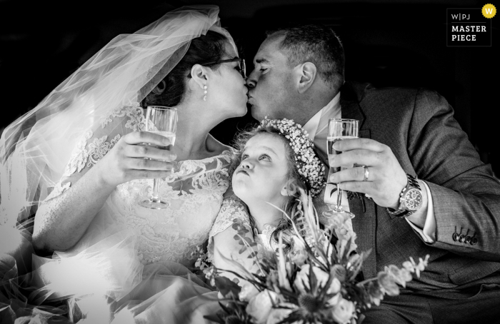 Best wedding photography from Wicklow, Ireland showing a pic ofa real candid moment in the car with the couple and a child during a private kiss with a toast