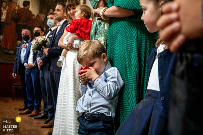 A top wedding photographer in Occitanie captured this picture ofA child monitoring rings at the City hall during the marriage ceremony