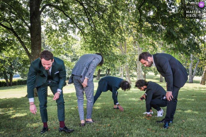 A top France wedding photographer at Château Saint Loup en Albret captured this picture ofthe groom and groomsmen searching the grass under the trees for an unknown object