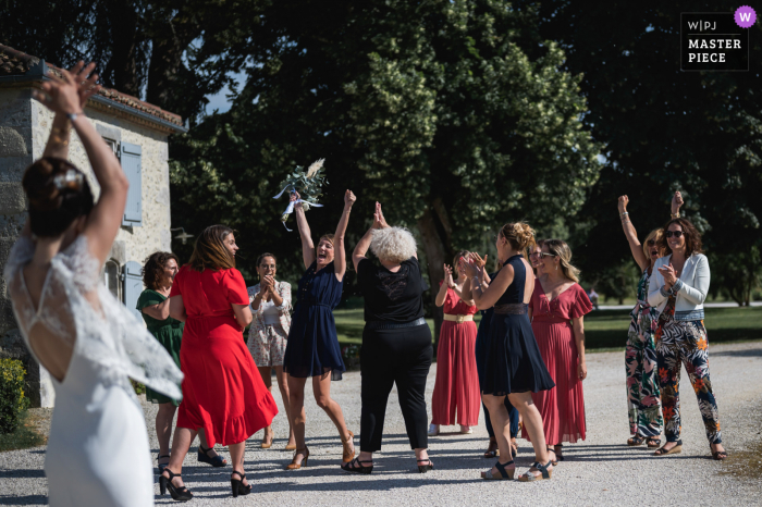 A France wedding photographer at Domaine de Pécarrère created this image ofthe bride tossing her bouquet outside to the women
