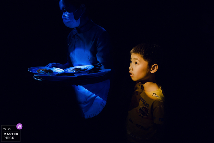 A top wedding photographer in Fujian captured this picture ofa Waiter and child serving dishes at the wedding ceremony