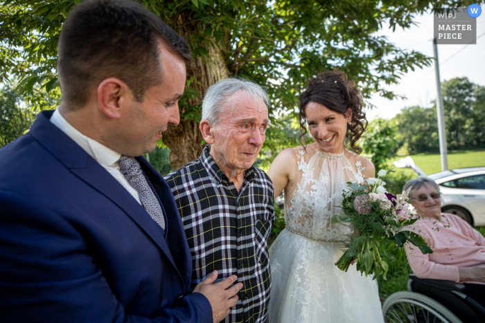 A wedding photographer in Occitanie created this image of Her handicapped grandpa is discovering Bride and groom after ceremony with emotion