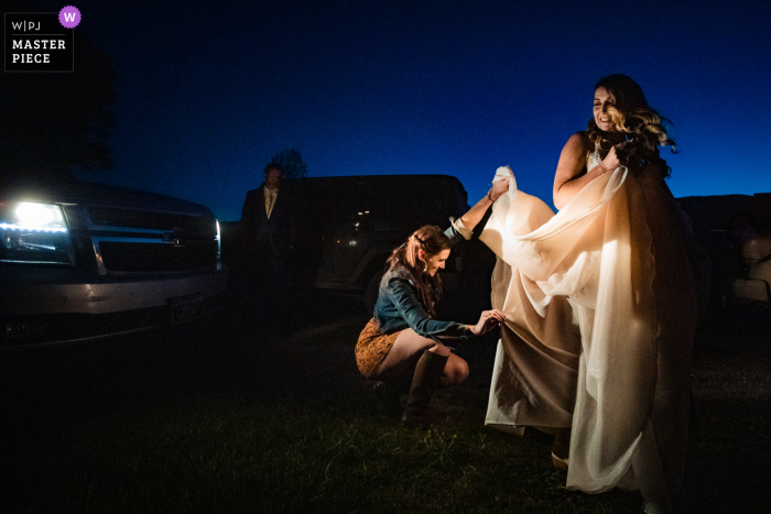 Best wedding photography from Emigrant, Montana showing a pic ofbustling the dress by headlights