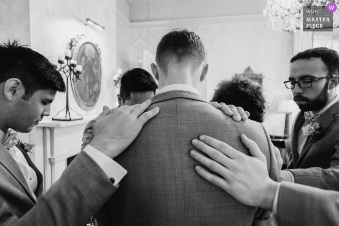 A San Antonio wedding photographer at The Argyle created this image ofThe groom with his back to the camera holds a prayer with groomsmen
