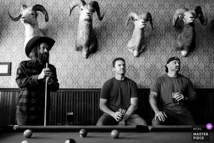 A top wedding photographer in Emigrant, Montana captured this picture in BW of Groomsmen playing pool