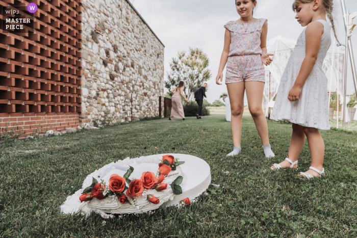 An Italian wedding photographer in Venice created this image ofShocked kids looking at the fallen wedding cake while, in the background, the angry bridesmaid is yelling at the guy responsible for it