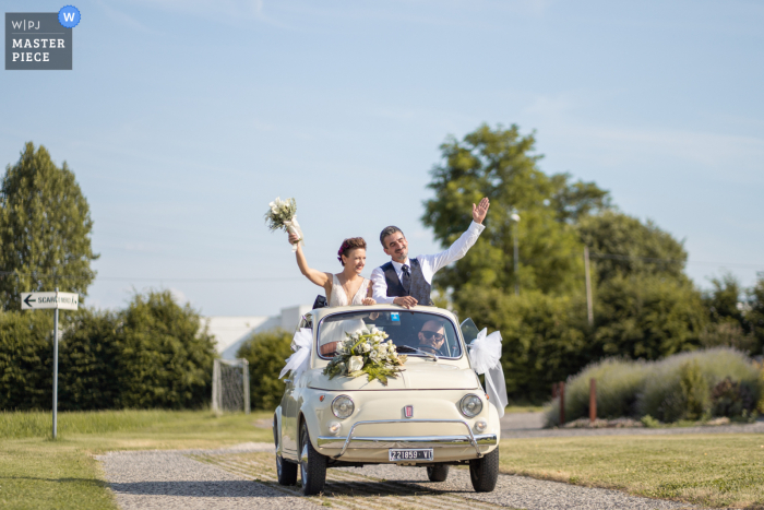 Best wedding photography from Venice showing a pic of The arrival of the newlyweds at the reception venue in a vintage convertible automobile