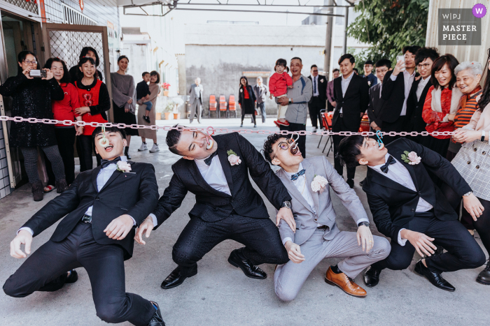 Taichung Taiwan wedding photography showing The groom and the best man go through the barriers