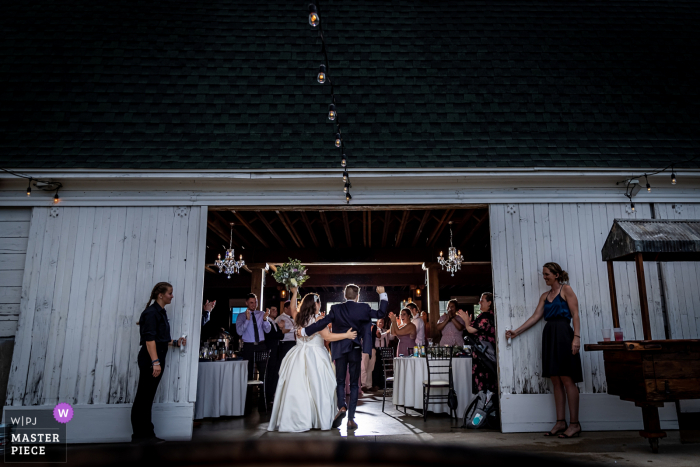 An Illinois wedding photographer at the Ashley Farm in Yorkville created this image ofthe couple being introduced as they enter the barn venue