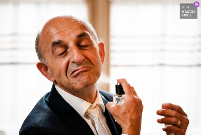 A France wedding photographer at Château du Croisillat in Caraman created this image showing Dad is getting ready with cologne