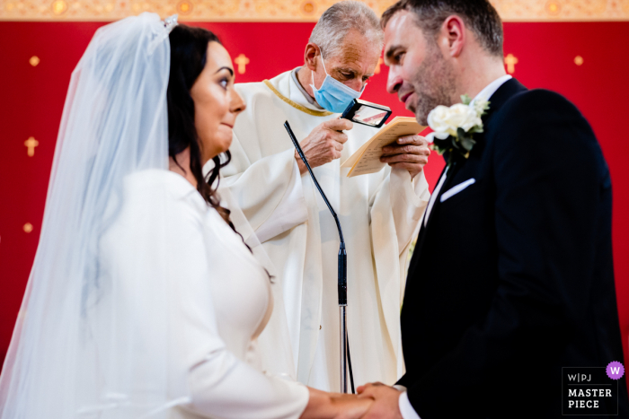 A top Ireland wedding reportage photographer at the CloughJordan House captured this picture showing Priest needs a little help reading the vows during the ceremony