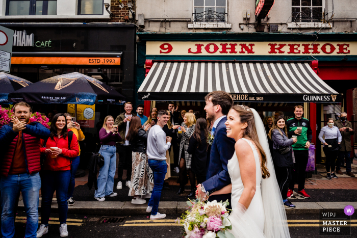 Dublin City best wedding reportage photography in Ireland showing a pic ofA crowd of revellers outdoor drinking during Covid rules react to seeing the newlyweds