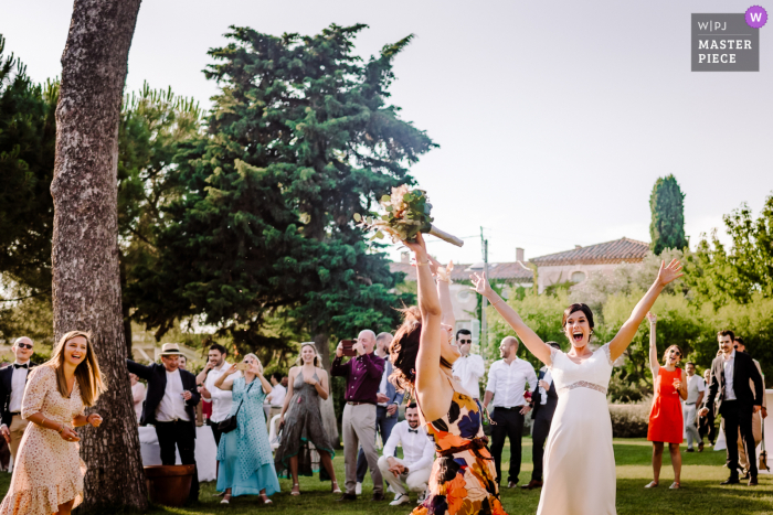 A top wedding photographer in Herault captured this picture at the Domaine Fon de Rey outdoors showing the Throwing of bouquet at a wedding