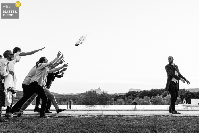A top wedding photographer at Mas Saint Germain in France captured this picture in BW showing The groom throws a gamepad to the single men
