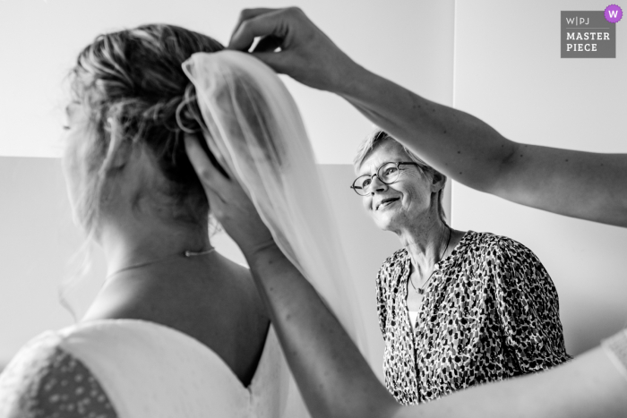 Netherlands best wedding reportage photography from Maassluis showing a pic ofa Proud mom looking when the veil is attached to the bride