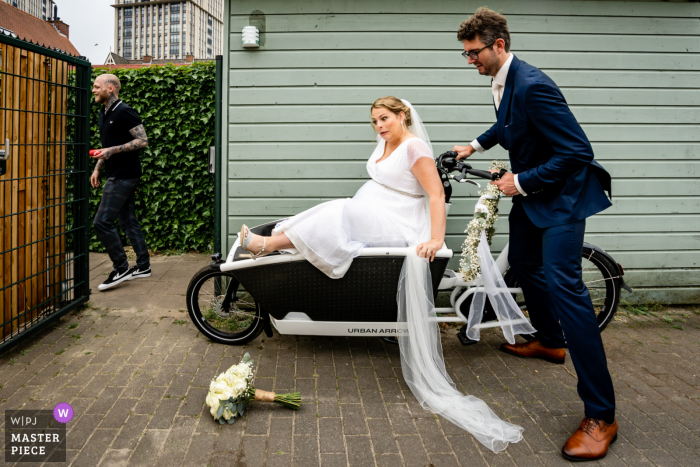 A top wedding photographer in Maassluis captured this picture ofthe Bride getting ready for her ride on a bike with the groom