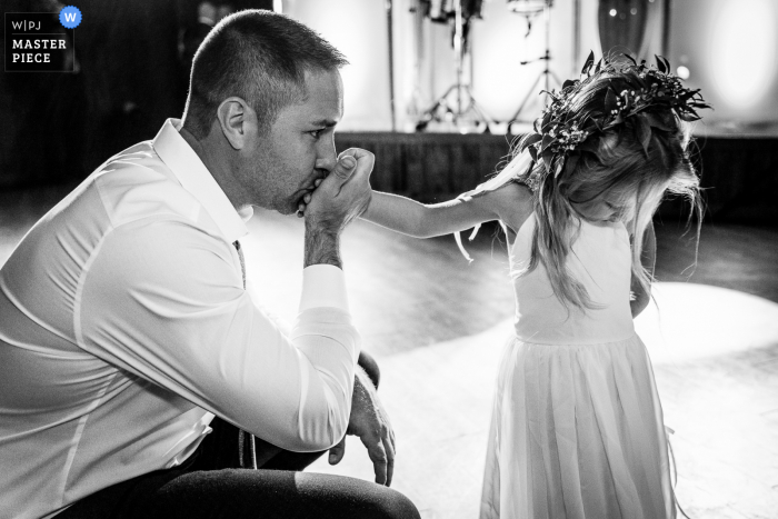 A top wedding photographer in Pennsylvania captured this picture showing Father of the flower girl attempting different bribery techniques to get his daughter to come and eat her dinner, He started by offering a ring pop