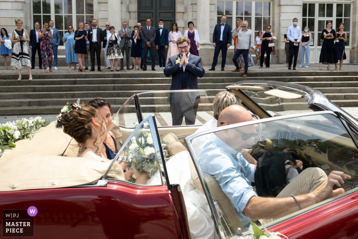 A top wedding photographer in Limoges captured this picture of the arrival of the bride in the back of a convertible vintage auto