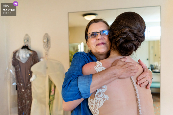 A San Diego wedding photographer at The Thursday Club created this image ofThe bride and her mother in a warm hug