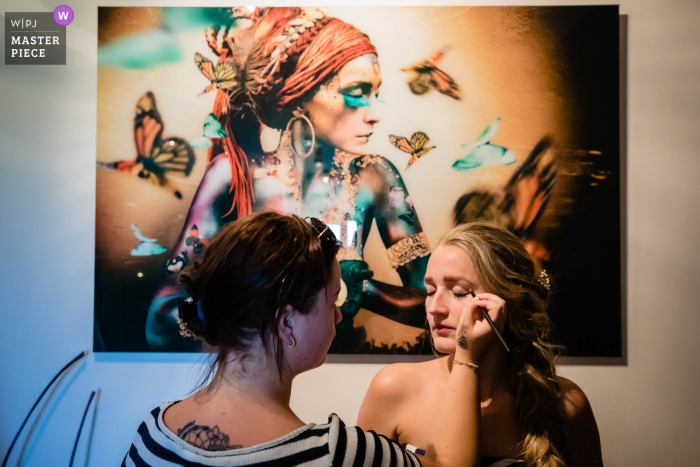 A top wedding photographer in Noord Brabant captured this picture ofthe bride getting ready near a painting on the wall