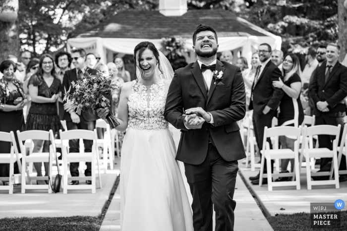 Colorado best wedding photography from Fort Collins showing a pic of A newly wed couple sharing a laugh as they exit their ceremony