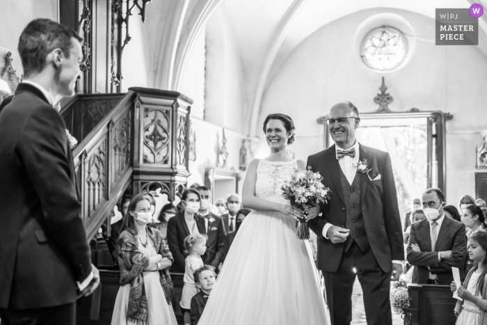 France best wedding photography from Domaine de Courson showing a pic ofa Moment of laughter inside the curch during the ceremony