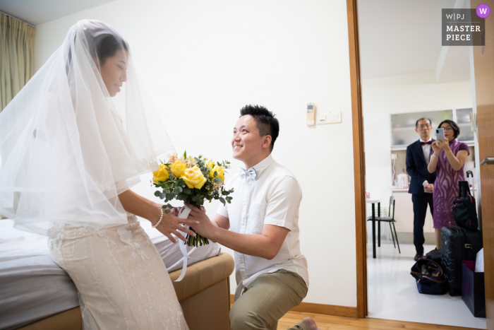 A wedding photographer in Singapore created this image ofthe Groom presenting the bouquet to his bride while her parents looked on