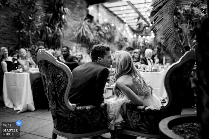 A top wedding photographer in Chicago, Illinois captured this picture showing the Couple has just sat down for dinner service and the guests started clinking their glasses