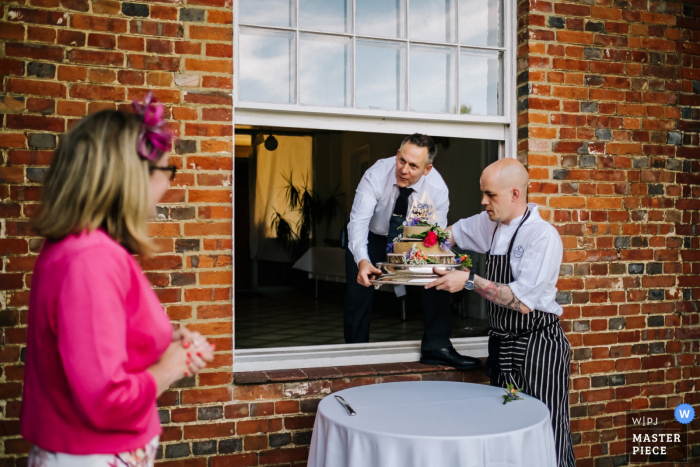 A UK wedding photographer at Rownhams House created this image of The caterers bringing the cake out a window
