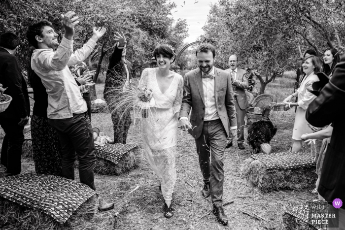 Best wedding photography from Occitanie showing a pic ofThe bride and groom leaving the secular ceremony to the applause of their guests