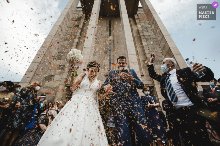 Best wedding photography from Porto, Portugal showing a pic ofa confetti shower for the bride and groom leaving the church