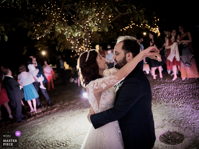 Italy best wedding photography from the Castello di Cernusco in Lombardone showing a pic of the bride and groom dancing while in the background all the guests watch them excitedly