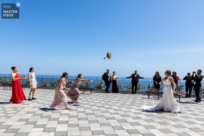 An Italian wedding photographer at Piazza IX Aprile in Taormina created this image ofbride tossing flower bouquet to single women outdoors by the sea