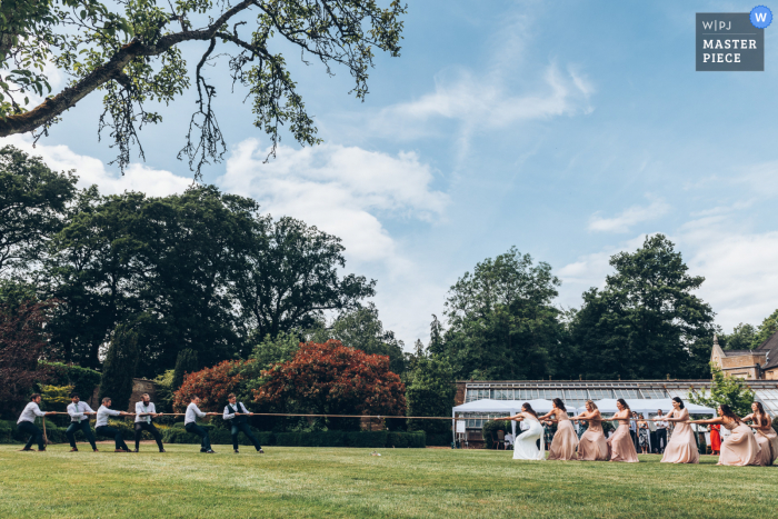 A top wedding photographer at Hanbury Manor in Hertfordshire captured this picture ofsome outdoor Wedding Tug of War on the grass