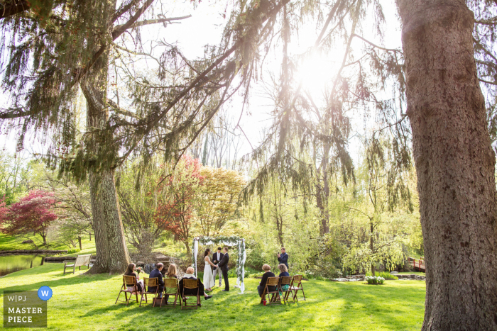 A wedding photographer at the Appleford Estate in Pennsylvania created this image showing Wide view of intimate outdoor ceremony under the mature trees