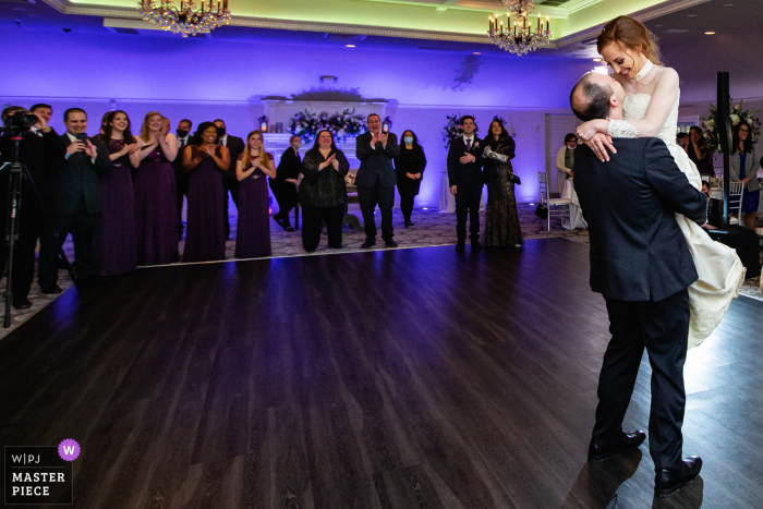 Best wedding photography from Castle at Skylands Manor in New Jersey showing a pic ofthe groom lifting up bride during first dance at the Castle