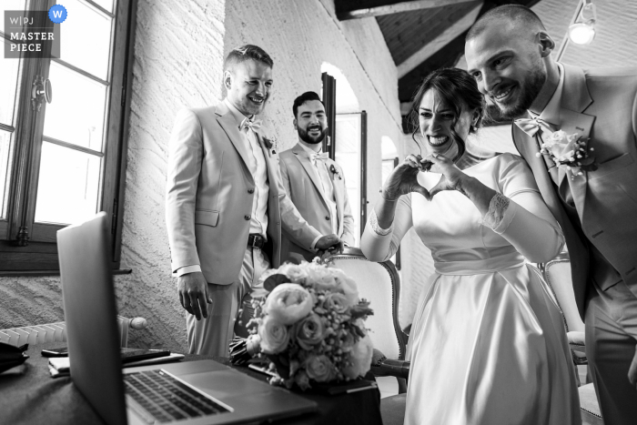 A top French wedding photographer at a town hall captured this picture ofThe bride crying and making a sign to sister on a screen not present because of covid-19