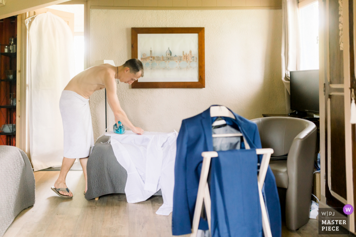 A top wedding photographer in Bordeaux, France captured this picture showing The groom irons his shirt before the ceremony