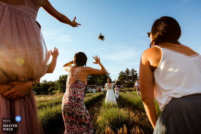 A wedding photographer in Paris created this image ofGirls fighting for the bouquet outside under a blue sky