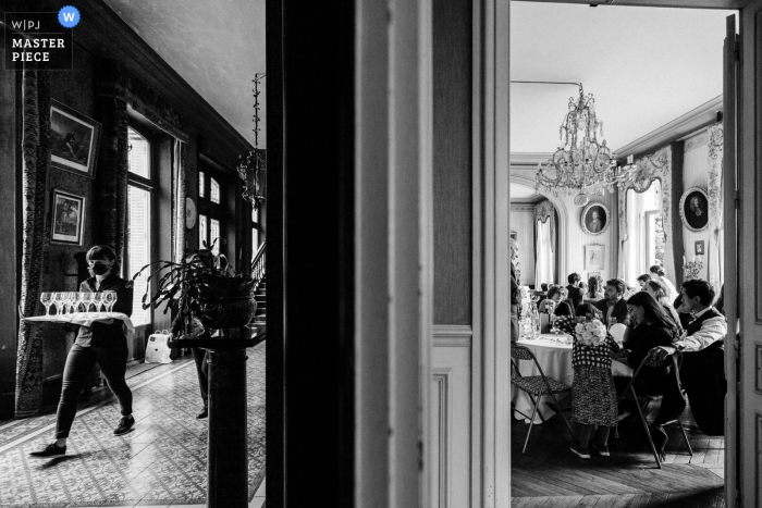 A top wedding photographer in Paris, France captured this picture ofa waitress bringing glasses to kitchen